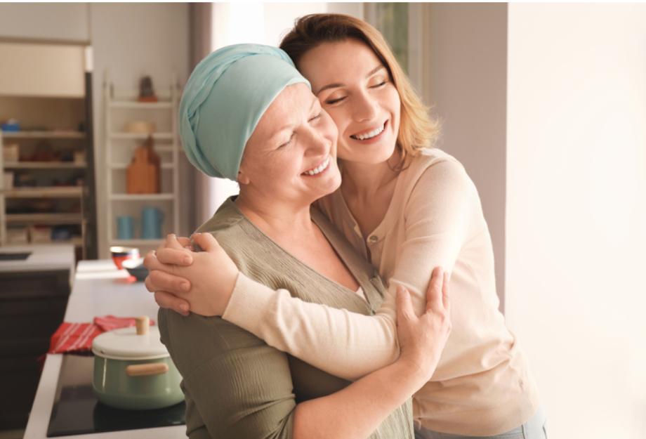 Filha abraçando mãe que está com câncer.
